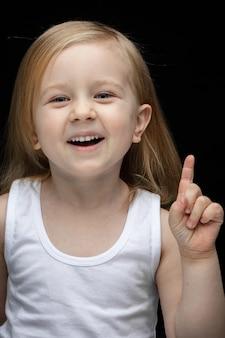 Schönes kleines mädchen im weißen unterhemd, das ihren finger nach oben zeigt und lächelt, während es auf schwarz steht
