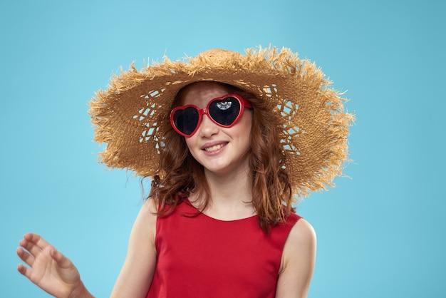 Schönes kleines mädchen in der herzbrille und im roten kleid