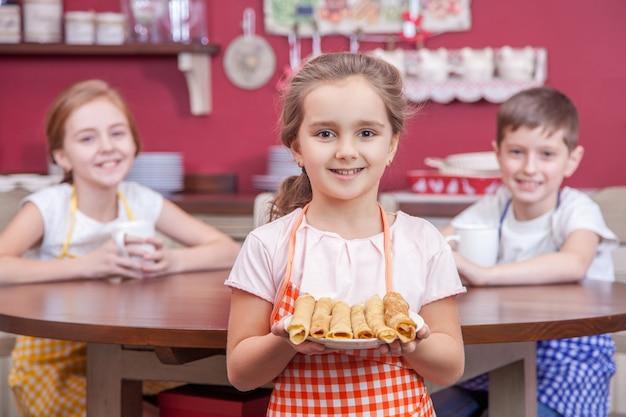 Schönes kleines mädchen in der küche, das einen teller mit pfannkuchen hält und in die kamera schaut studioaufnahme