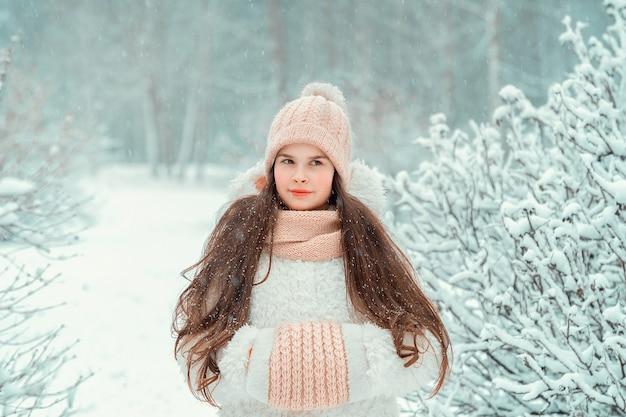 Schönes kleines mädchen in der strickmütze auf winterwald. warme weiße winterkleidung, die positivität ausdrückt