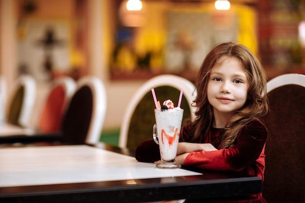 Schönes kleines mädchen in einem burgunderfarbenen kleid mit einem milchshake in einem restaurant