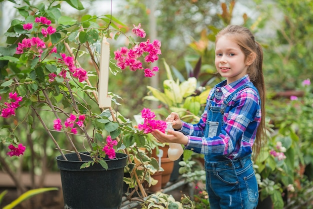 Schönes kleines mädchen in einem gewächshausgarten, der sich um blühende pflanzen kümmert
