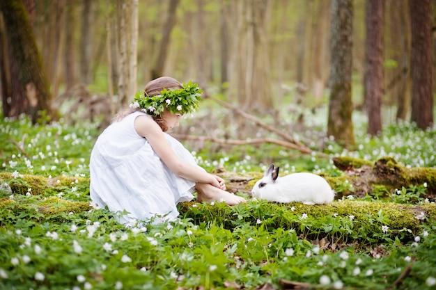 Schönes kleines mädchen in einem weißen kleid, das im frühjahr mit weißem wald des kaninchens plaing ist