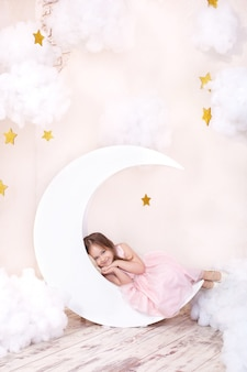 Schönes kleines mädchen liegt im studio mit dekor von mond, sternen und wolken. kind träumt. kleines süßes mädchen sitzt auf einem dekorativen mond mit baumwollwolken und sternen. gesundes schlafkonzept. kindheit