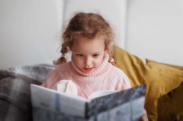 Schönes kleines mädchen liest ein buch, das auf der couch sitzt
