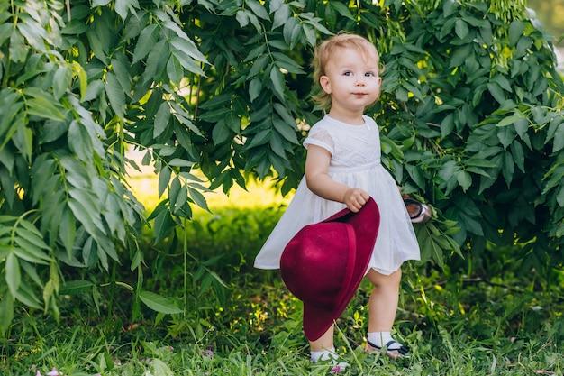 Schönes kleines mädchen mit blondem haar in einem weißen kleid im sonnigen sommertag des parks.