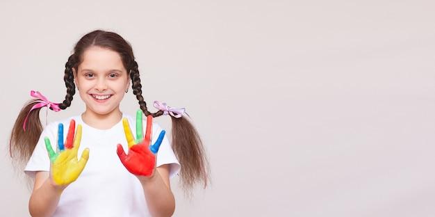 Schönes kleines mädchen mit den händen in der farbe