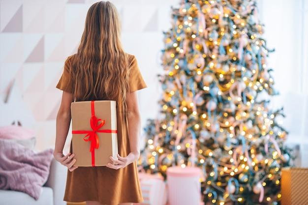 Schönes kleines mädchen mit einem geschenk. rückansicht des kindes hält eine geschenkbox nahe dem weihnachtsbaum drinnen. frohe weihnachten und schöne feiertage.