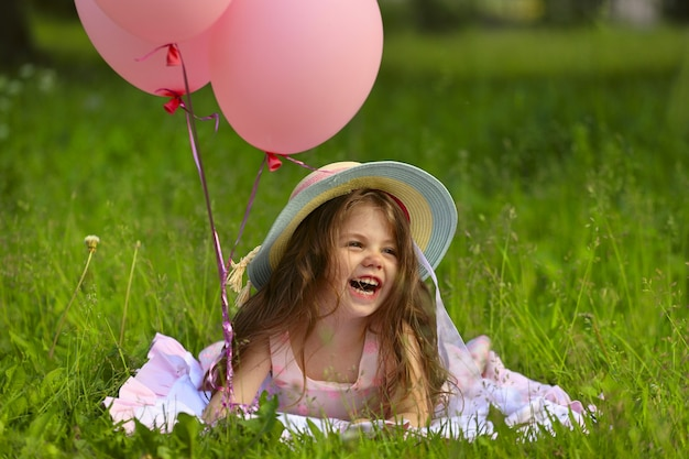 Schönes kleines mädchen mit hut und ballons lachen. foto in hoher qualität