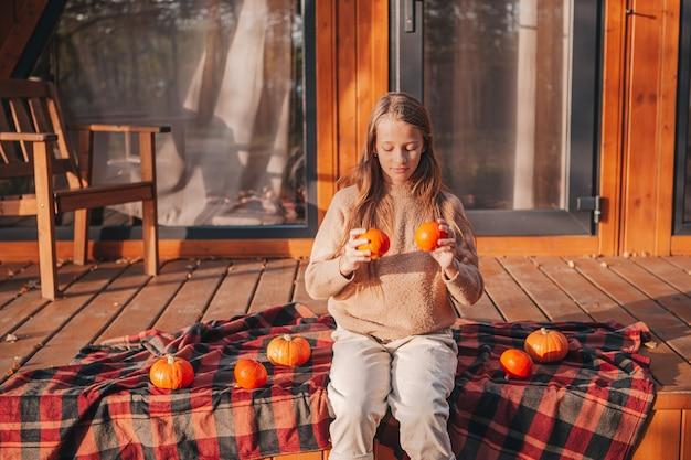 Schönes kleines mädchen mit kürbissen, die herbsttag auf der terrasse genießen. halloween tage