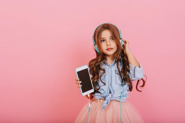 Schönes kleines mädchen mit langen brünetten haaren mit telefon, das musik durch blaue kopfhörer lokalisiert auf rosa hintergrund hört. fröhliche stimmung des kleinen kindes, musik genießend