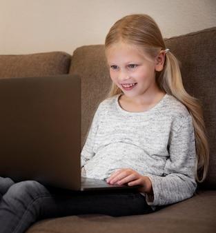 Schönes kleines mädchen mit laptop zu hause