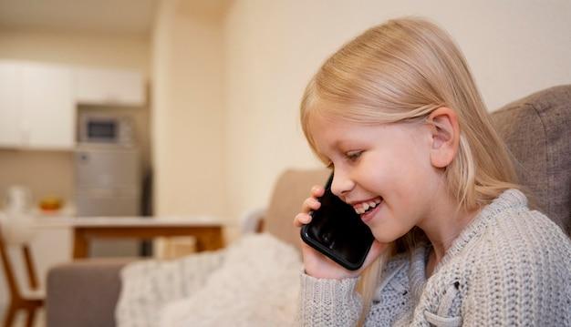 Schönes kleines mädchen mit smartphone zu hause