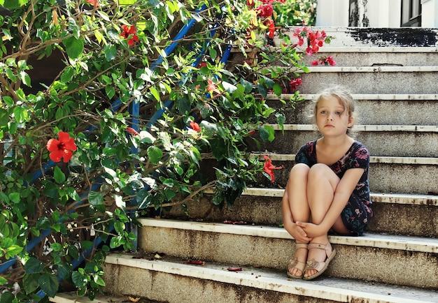 Schönes kleines mädchen sitzt auf alten treppen nahe blumen