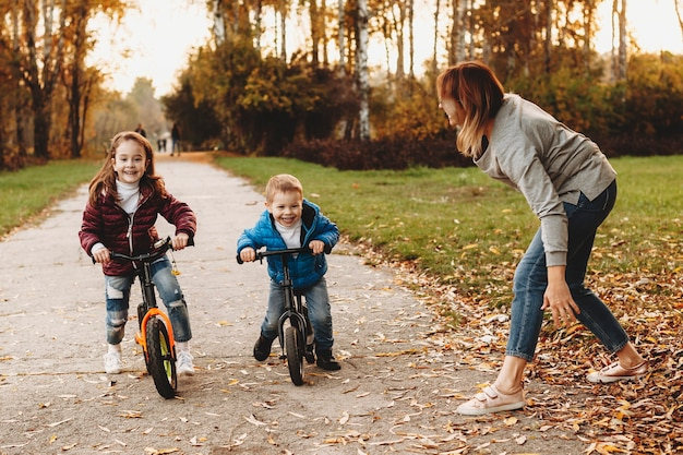 Schönes kleines mädchen und ihr bruder mahlen auf den fahrrädern im park, während ihre mutter ihnen den start gibt.