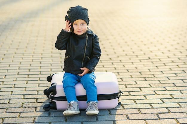 Schönes kleines reisendes mädchen sitzt auf rosa koffer und spricht auf handy nahe flughafen