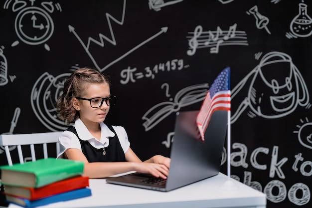 Schönes kleines schulmädchen am schreibtisch vor schwarzem hintergrund mit usa-flagge