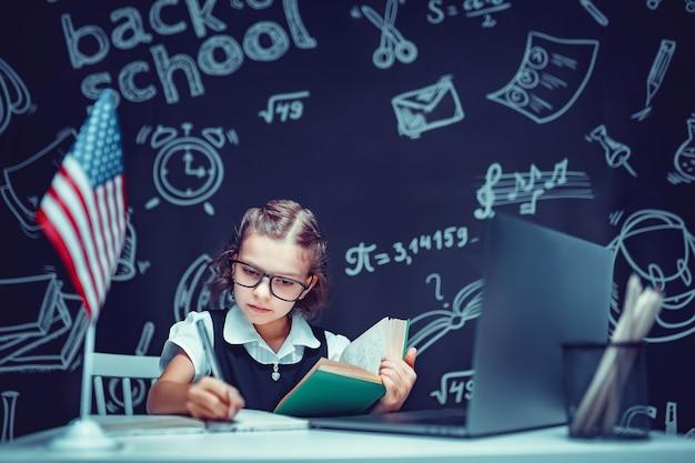 Schönes kleines schulmädchen, das am schreibtisch sitzt und online mit laptop vor schwarzem hintergrund mit ...