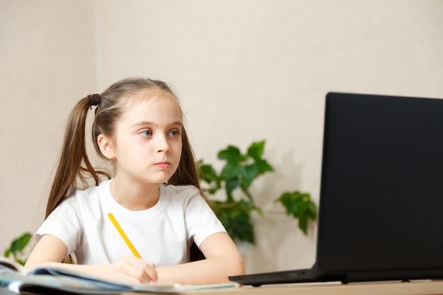Schönes kleines schulmädchen, das zu hause in ihrem zimmer mit einem laptop und klassennotizen arbeitet, die in a studieren