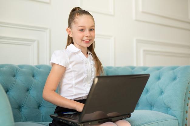 Schönes kleines teenager-mädchen in einem weißen hemd sitzt auf einem sofa mit einem laptop