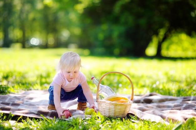 Schönes kleinkindkind, das ein picknick im sonnigen park hat