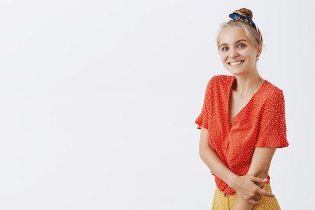 Schönes kokettes blondes mädchen errötend und lächelnd