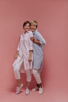 Schönes kurzhaariges mädchen in den weißen und rosa kleidern, die mit blonder dame im gestreiften hemd auf lokalisiertem hintergrund lächeln und posieren.