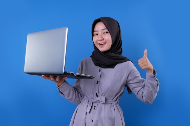 Schönes lächeln der asiatischen frau bringen einen laptop und sagen okay ausdruck