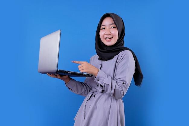 Schönes lächeln der asiatischen frau, das einen laptop zeigt und etwas schaut