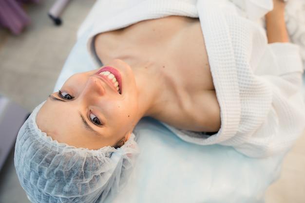 Schönes lächeln der geduldigen frau, das auf bett im operationsraumkrankenhaus liegt