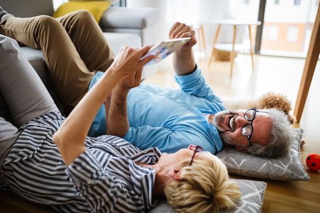Schönes lächelndes älteres paar, das spaß beim verwenden des tablets zu hause hat?