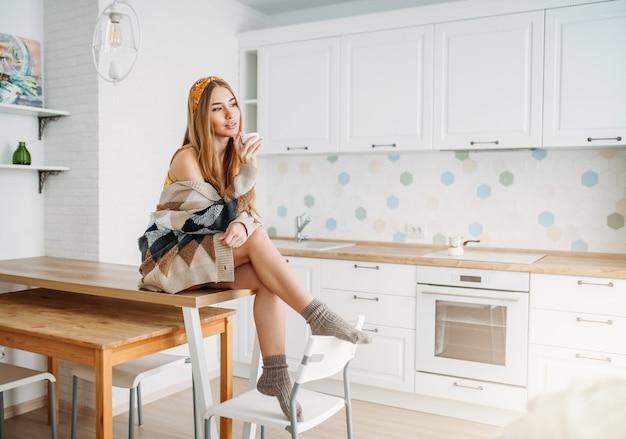 Schönes lächelndes angemessenes langes haarmädchen der jungen frau, das in der gemütlichen gestrickten wolljacke mit schale morgen cofee zu hause sitzt auf küchentisch trägt