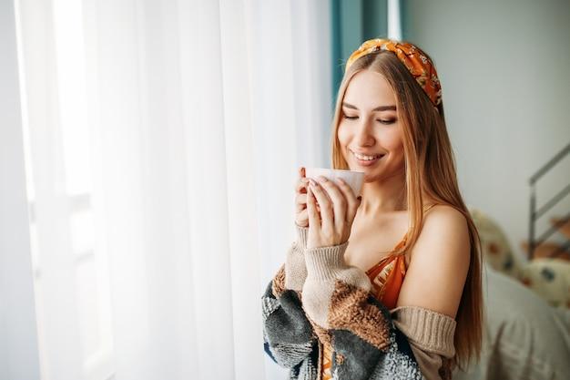 Schönes lächelndes angemessenes langes haarmädchen der jungen frau, das zu hause in der gemütlichen gestrickten wolljacke mit tasse tee nahe fenster trägt