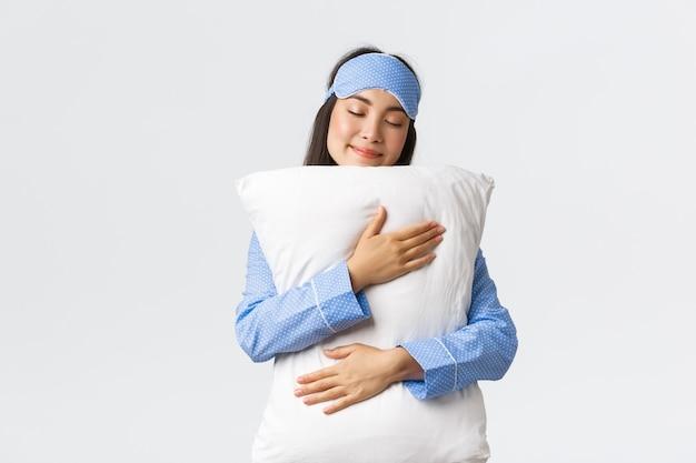 Schönes lächelndes asiatisches mädchen in schlafmaske und pyjama, das einen süßen traum hat, kissen mit dummem grinsen und geschlossenen augen umarmt, auf weißem hintergrund steht, unwilliges aufwachen.