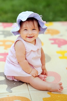 Schönes lächelndes baby, das im garten spielt. glückliches nettes kleinkind, das spaß im park hat. süßes sonniges mädchen im panama-hut