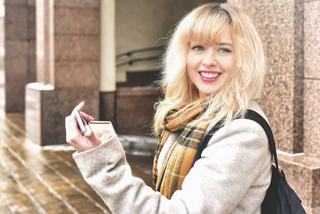 Schönes lächelndes blondes kaukasisches mädchen, das in der stadt geht und ihr make-up begradigt, das in den make-up-spiegel schaut