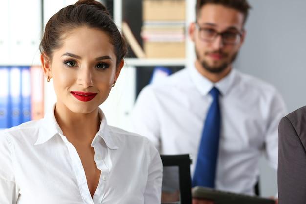 Schönes lächelndes brünettes schreibermädchen am arbeitsplatz