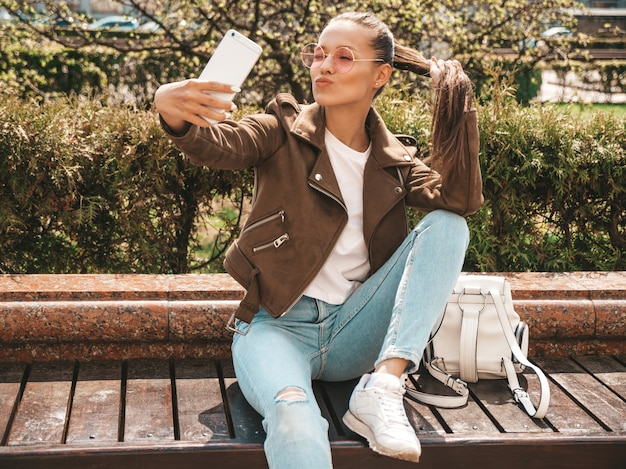 Schönes lächelndes brunettemädchen in der sommerhippie-jacke und -jeans vorbildliches nehmendes selfie auf smartphone