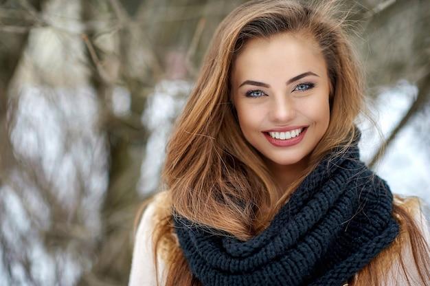 Schönes lächelndes frauenwinterporträt
