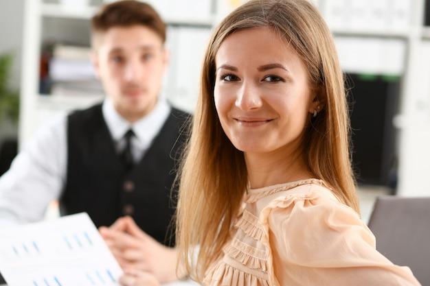 Schönes lächelndes fröhliches mädchen am arbeitsplatz, das direkt mit kollegengruppe im hintergrund schaut.