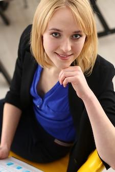 Schönes lächelndes geschäftsfrauenporträt am arbeitsplatz, das aufwirft. angestellter