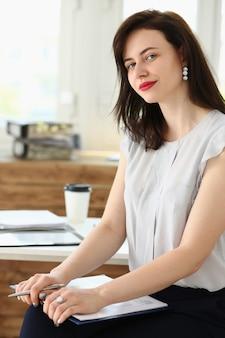 Schönes lächelndes geschäftsfrauenporträt am arbeitsplatz, der direkt schaut