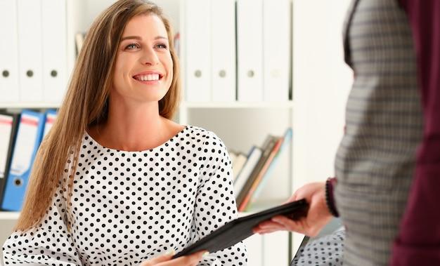 Schönes lächelndes geschäftsfrauporträt am arbeitsplatz