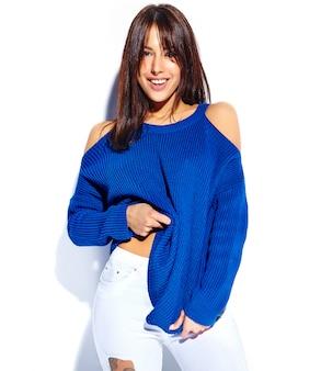 Schönes lächelndes hipster-brünettenfrauenmodell, das stilvollen blauen sommerpullover lokalisiert auf weißem hintergrund zieht