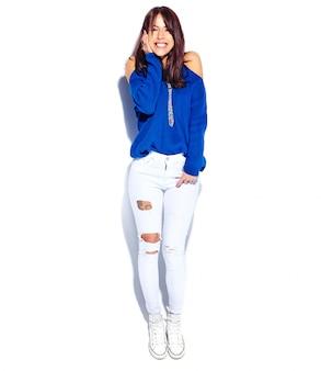 Schönes lächelndes hipster-brünettenfrauenmodell im lässigen stilvollen sommerblauen pullover lokalisiert auf weißem hintergrund. volle länge