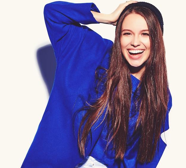 Schönes lächelndes hipster-brünettenfrauenmodell im stilvollen blauen mantel lokalisiert auf weiß