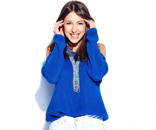 Schönes lächelndes hipster-brunette-frauenmodell im lässigen stilvollen blauen sommerpullover lokalisiert auf weißem hintergrund
