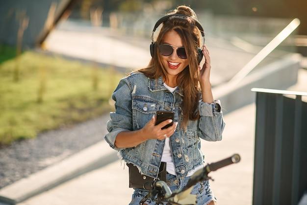 Schönes lächelndes junges mädchen, das lässige sommerkleidung trägt, sitzt auf einem fahrrad draußen im städtischen raum und hört musik mit drahtlosen kopfhörern mit handy. moderne intelligente technologie.