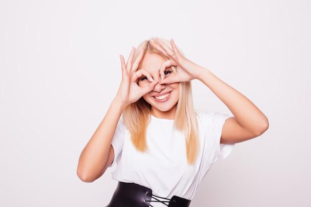 Schönes lächelndes junges mädchen zeigt brille aus den fingern,