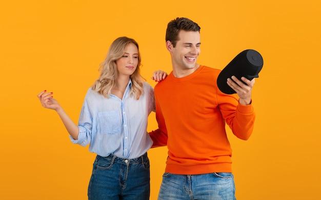 Schönes lächelndes junges paar, das drahtlosen lautsprecher hält, der musik hört, die auf orange tanzt